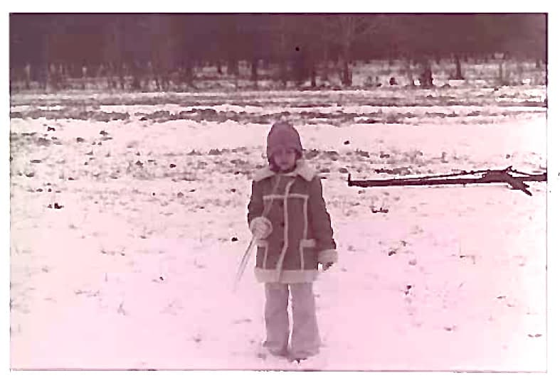little girl in a denim coat holding a long icicle